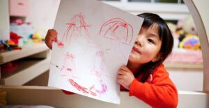 little girl child showing a drawing to the camera