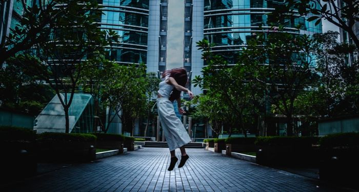 a woman who appears to be levitating off the ground in front of a glass skyscraper https://unsplash.com/photos/rFrkhK7wuHs