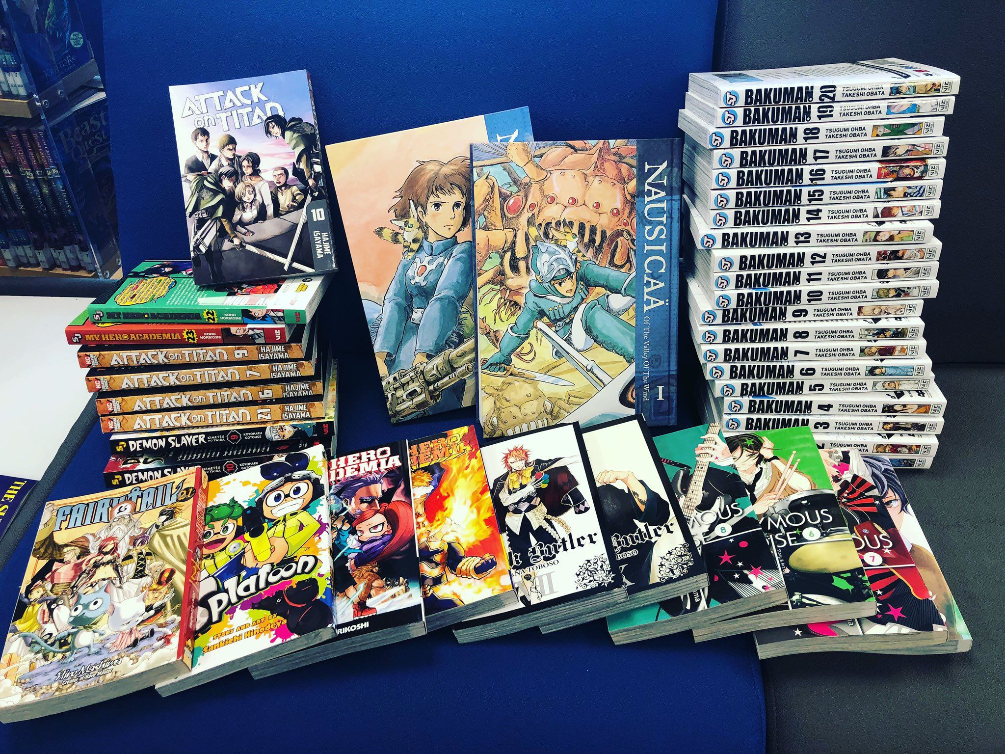 An assortment of manga on a library seat including Bakuman, Splatoon and more.