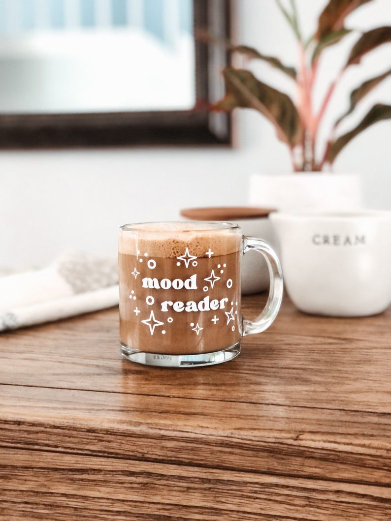 a glass mug with the words mood reader sitting on a brown table