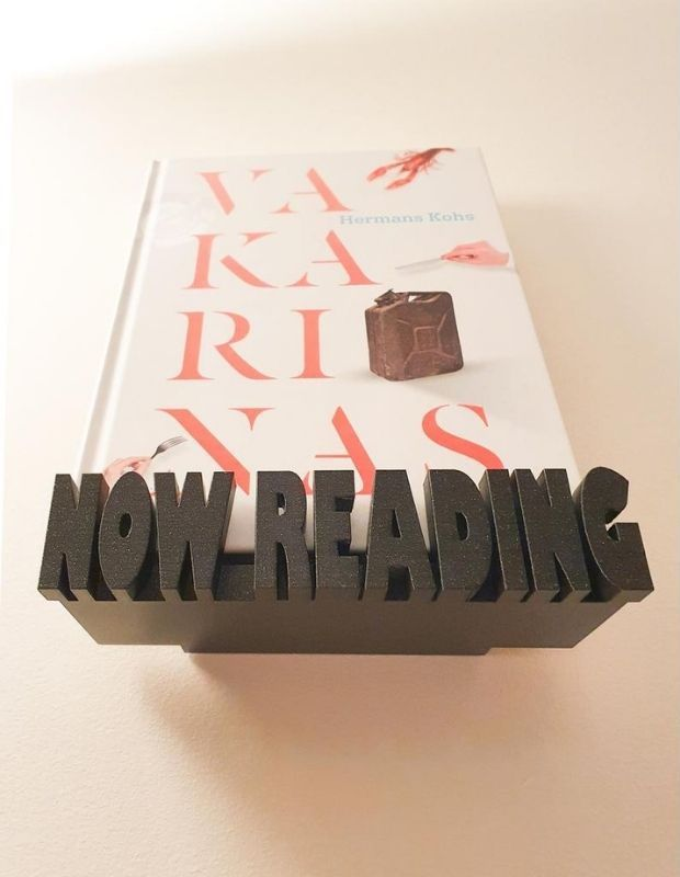 """Wooden floating shelf with """"Now Reading"""" lettering on front ledge"""