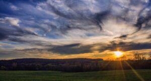 green grass field under cloudy sky at sunset https://unsplash.com/photos/Y5lV93pBqUw