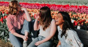 three young women laughing and sitting on a bench in a field of tulips https://unsplash.com/photos/cIfLUEZYLVg
