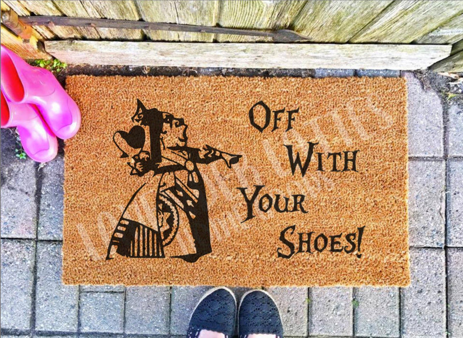 """Image of a brown doormat with an image of Alice in Wonderland's Queen of Hearts. Text reads """"Off With Your Shoes!"""""""