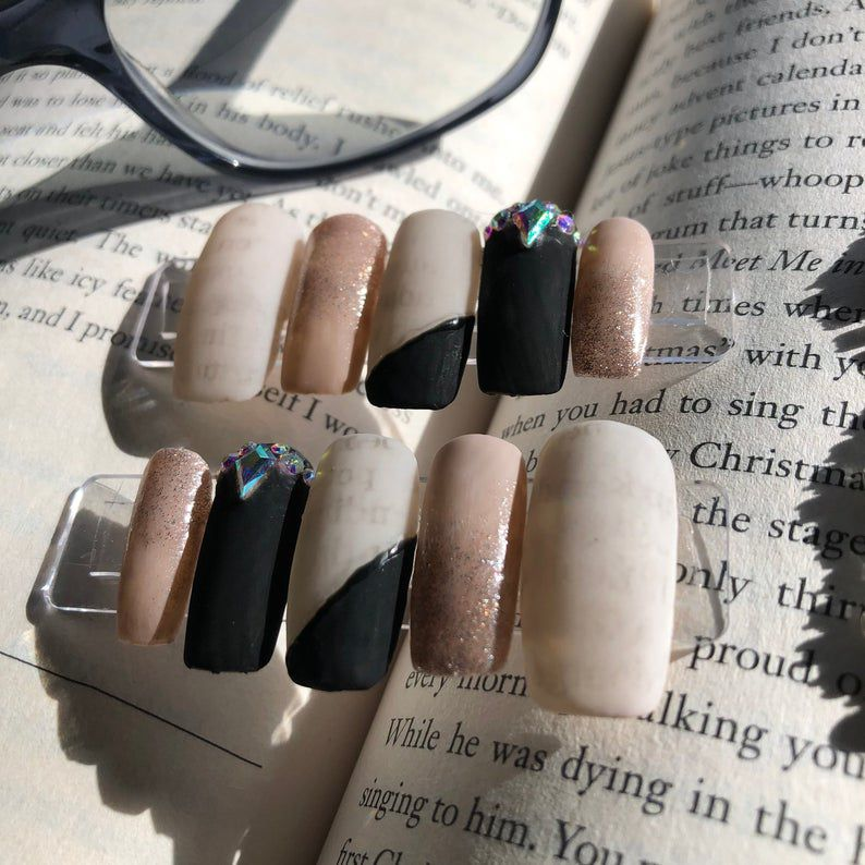 Image of taupe, white, and black nails with book page text on them.