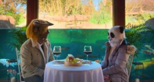 still frame from Netflix's SEXY BEASTS: two people sitting across from one another at a small white table, one dressed in a panda costume and the other as a bull