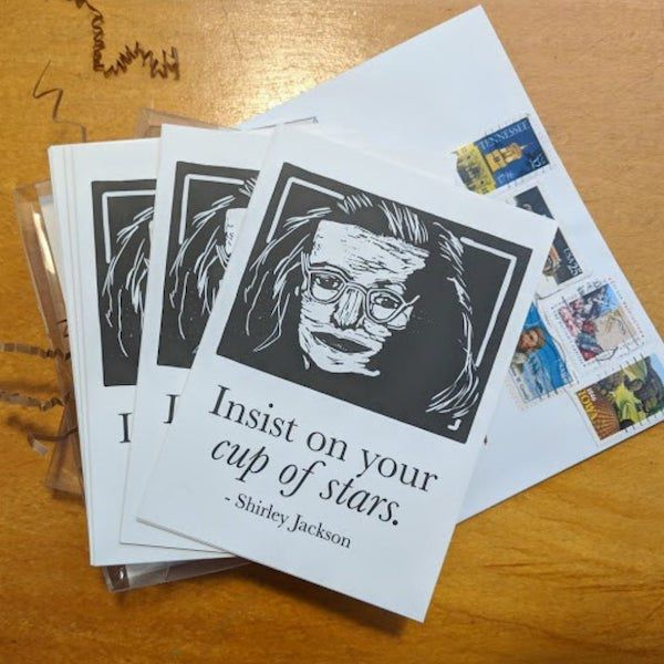 """a linocut portrait of the author, a white woman wearing glasses, with the words """"insist on your cup of stars"""""""