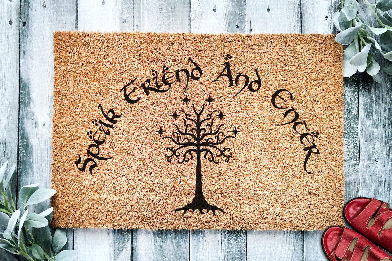 """Doormat with words """"Speak Friend and Enter"""" in black and a tree in the middle."""