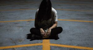 spooky image of girl sitting cross legged on asphalt with her hair covering her face https://unsplash.com/photos/uf12t-rLl2Q