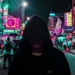 hooded figure in black colorful in colorful city at night