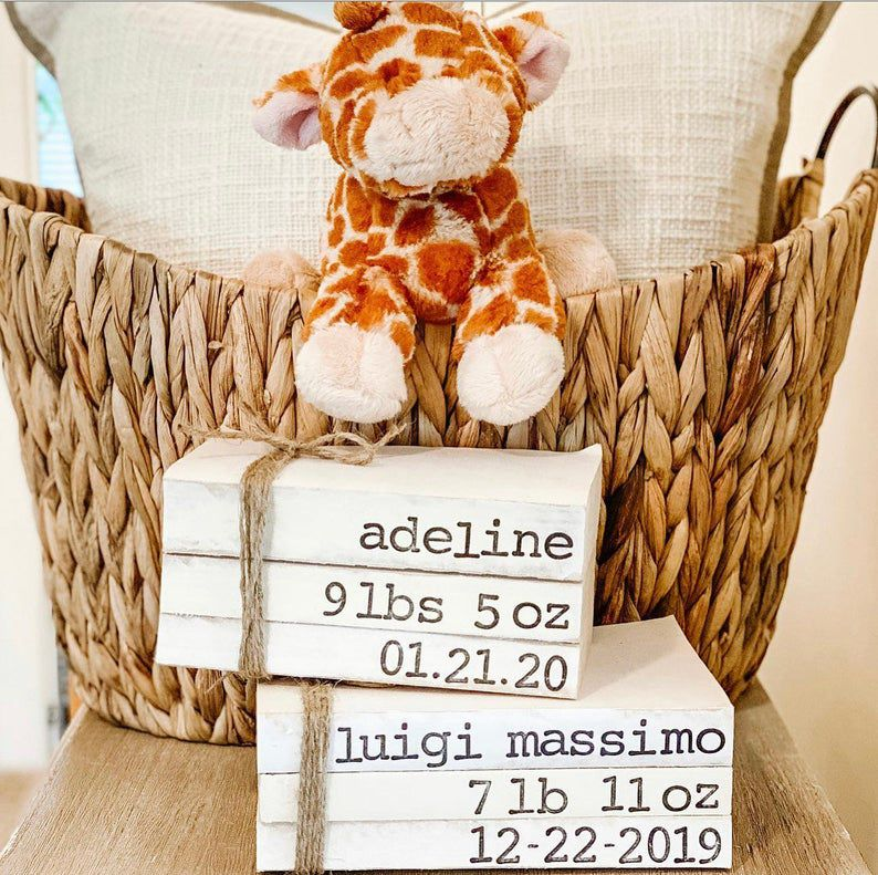Image of customized cream colored book stacks with baby name, birth date, and weight.