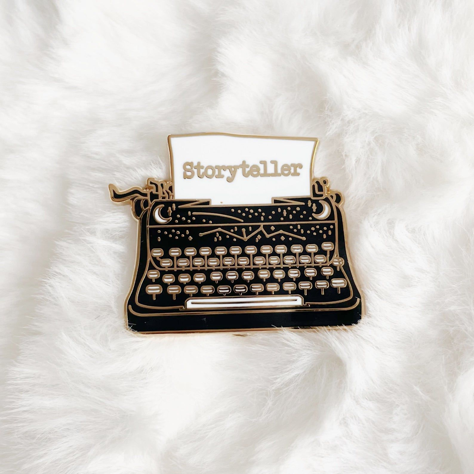 """Image of black typewriter pin with white paper. text on paper reads """"storyteller."""""""