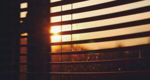 sunset as seen from behind dark window blinds https://unsplash.com/photos/UW6MVp5nOas