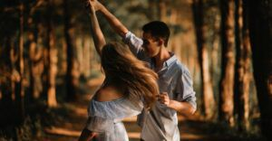 teen couple dancing with each other outside