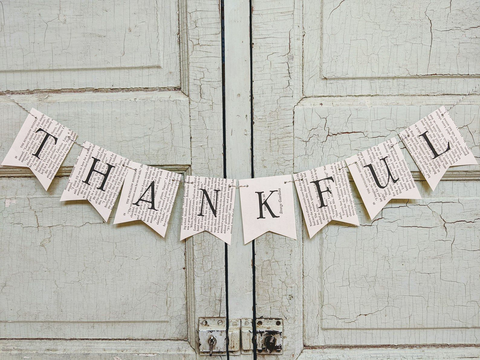 """Banner made out of old book pages. Each page has a letter, spelling out """"thankful."""""""