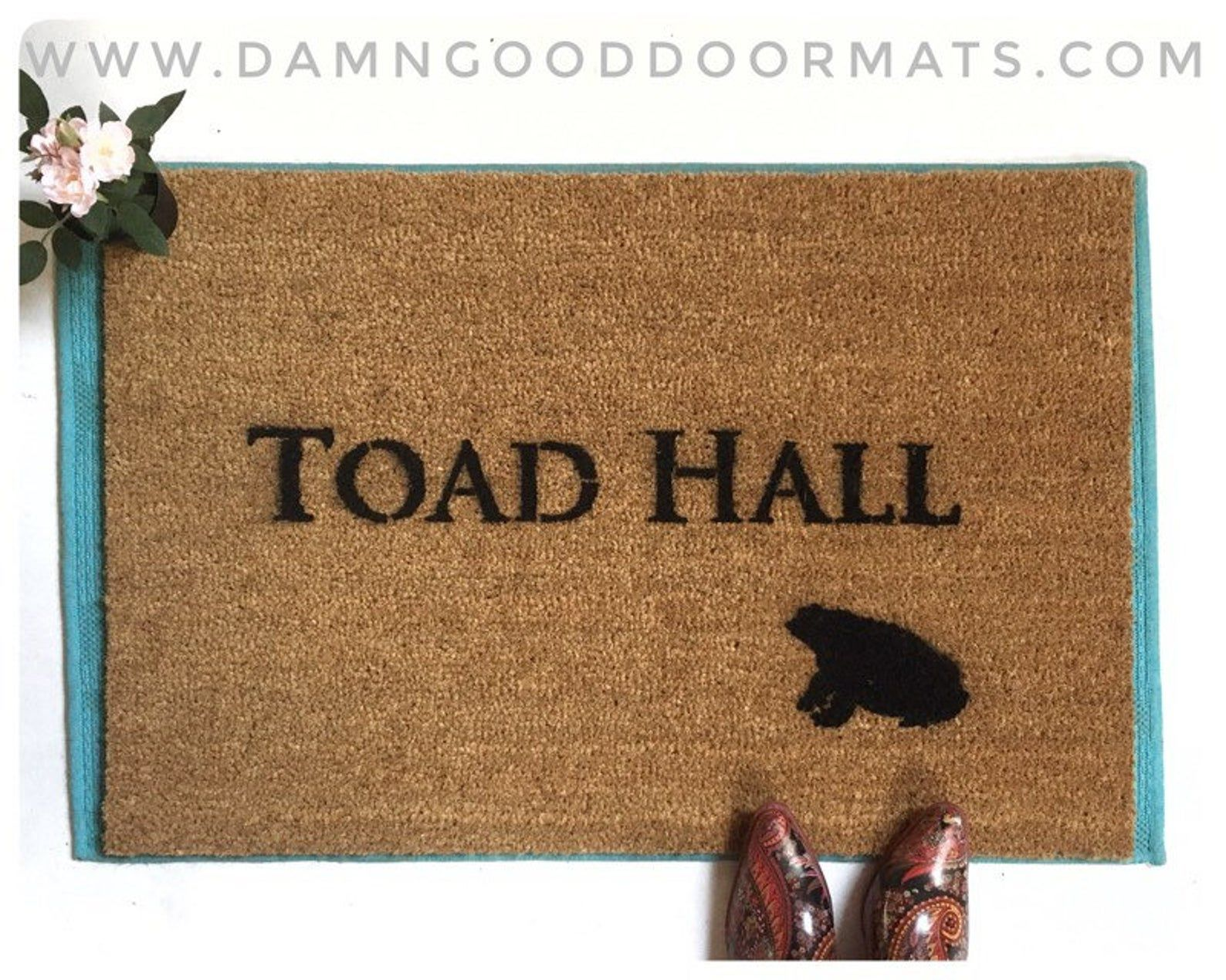 """Hand painted letters reading """"toad hall"""" with a small frog on a brown doormat. There is a pair of witchy shoes on the mat."""