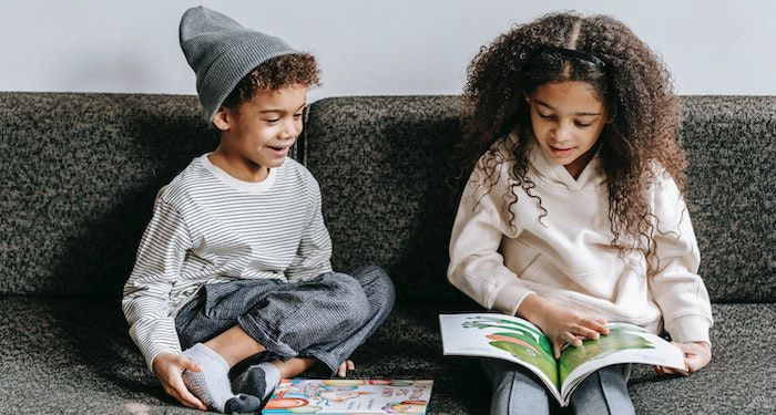 two kids reading on couch