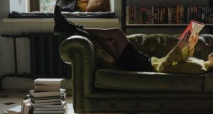 woman reading on couch with stack of books