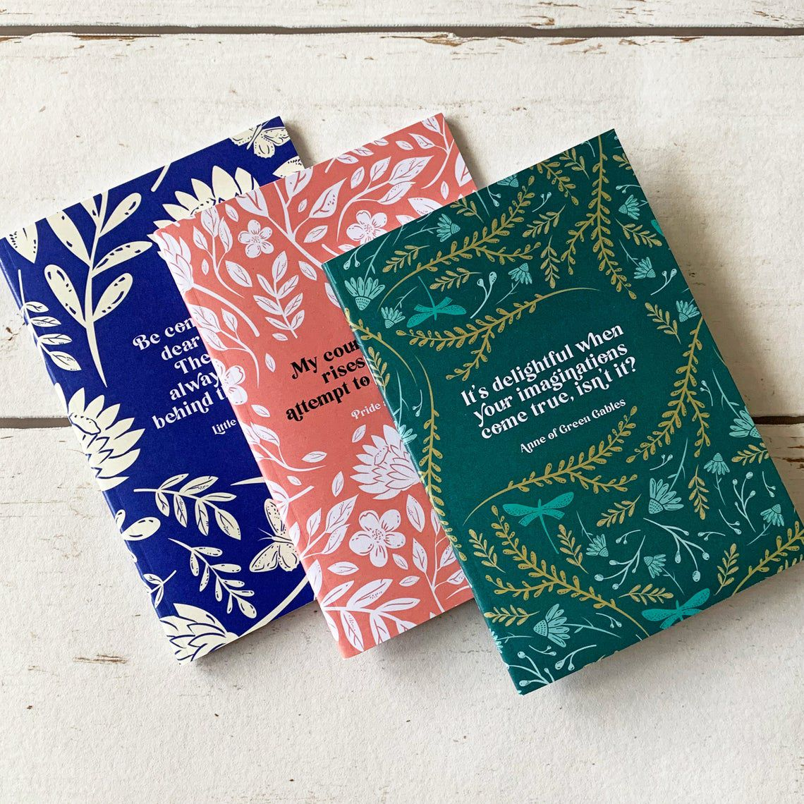 women of literature notebooks, colored blue, red, and green, with quotes from classic heroines