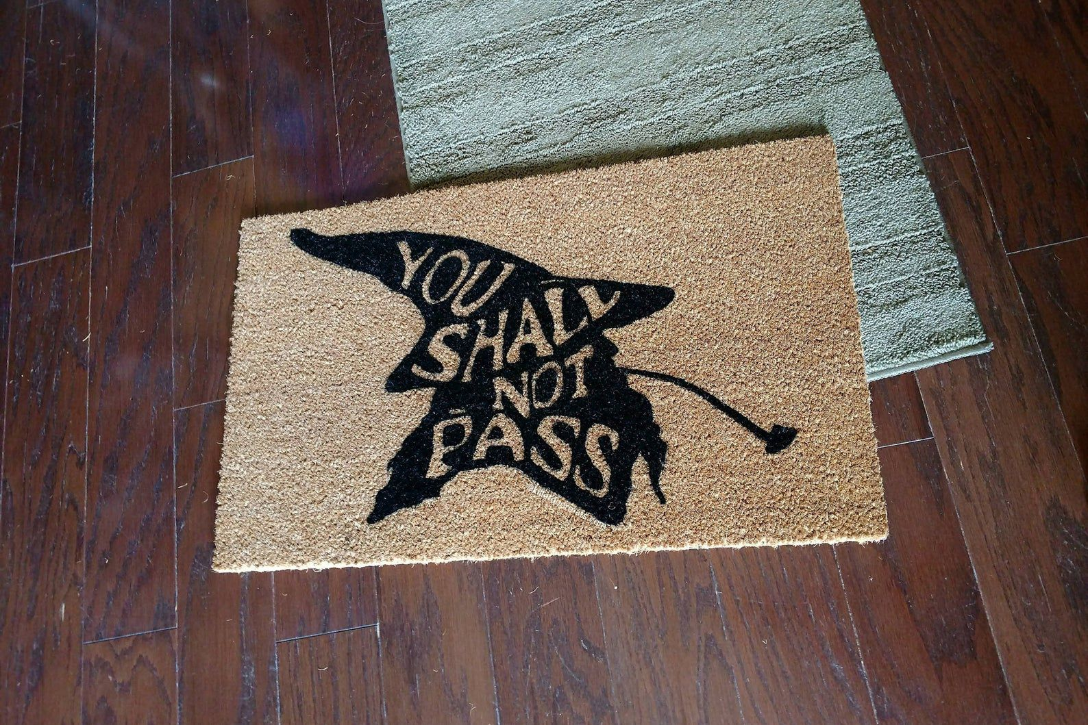 """Image of doormat with a wizard-like silhouette and inside of it, the words """"you shall not pass."""""""