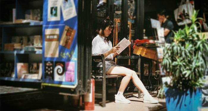 Asian woman reading outside bookstore