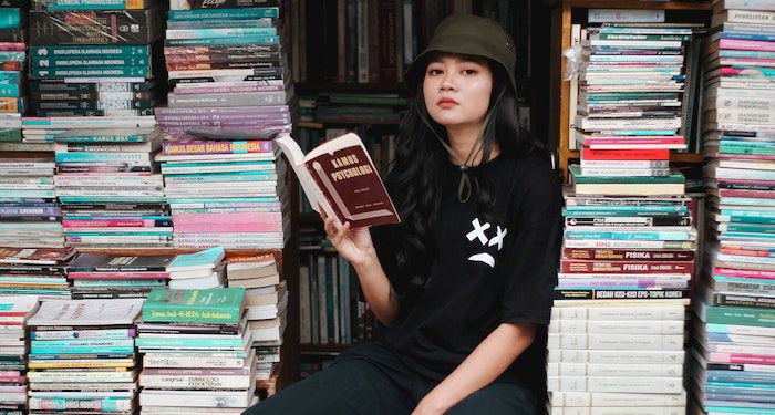 Asian woman reading surrounded by books at bookstore