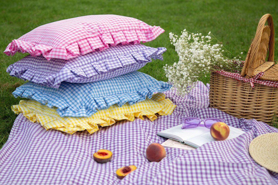 Gingham cushion covers on a blanket on the grass