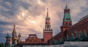 A landscape of Moscow under a bright cloudy sky, showing the towers of St Basil's Cathedral and the high red walls of the Kremlin