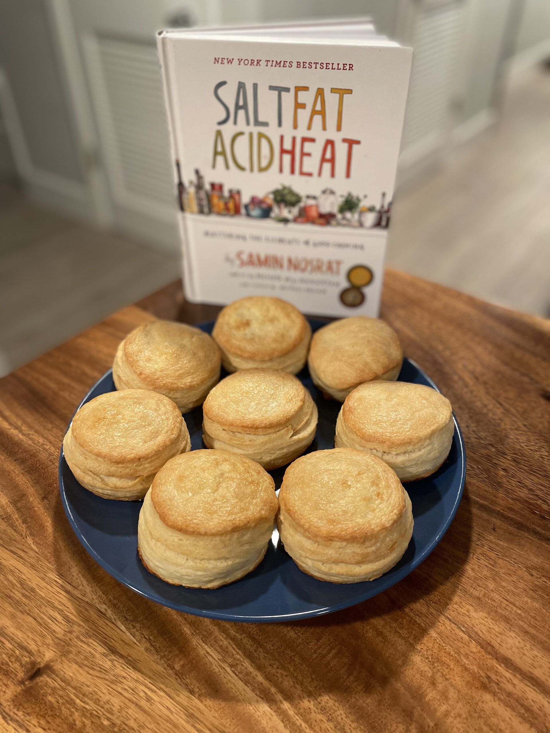 Salt, Fat, Acid, Heat cookbook with a plate of buttermilk biscuits