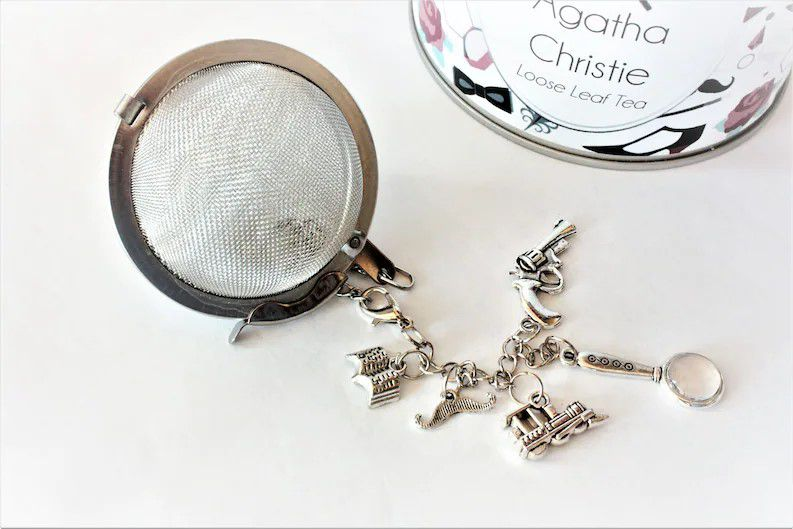 ball style tea infuser with charms of an open book, handlebar mustache, train, magnifying glass, and gun, all silver.