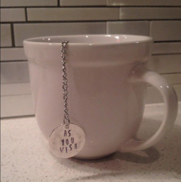 """tea infuser with a silver charm at the end of a chain that says """"as you wish"""" stamped on it"""