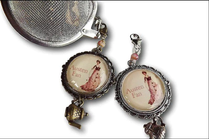 ball tea infuser with a bronze teapot charm and a cabochon with an image of a Georgian era girl with the text Austen fan on it