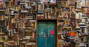 image of blue wooden door surrounded by book covered wall