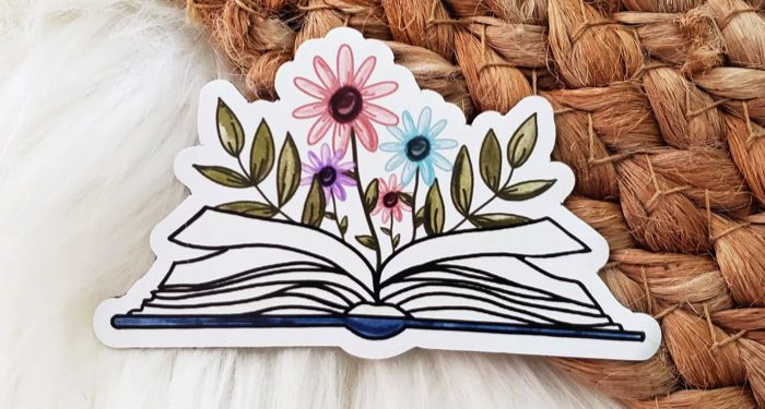 a magnet featuring an open book with pink, blue, and purple flowers growing from the center