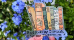 """A clear sticker that depicts beautiful antique book spines and reads """"Read Books and Dismantle Systems of Oppression"""""""