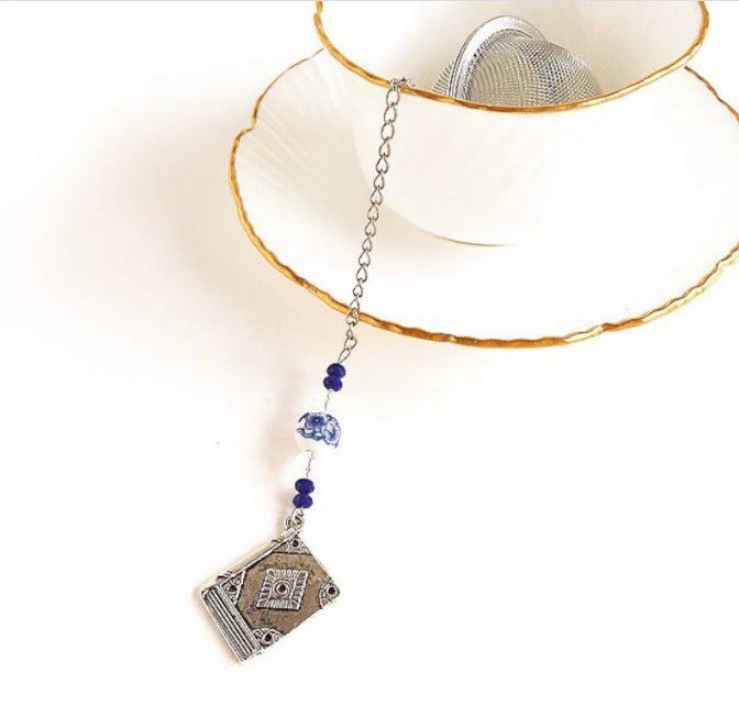 ball tea infuser with four dark blue beads, two clear beads, all split in half by a blue floral porcelain bead. At the end of the chain with the charms there is a silver book.