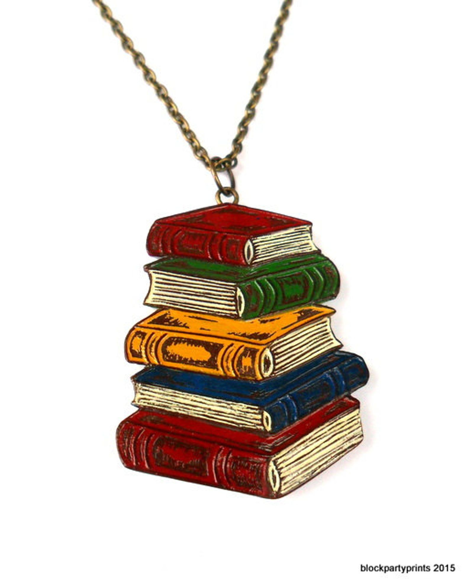 A pendant of red, green, blue, and yellow antique looking books on a bronze chain.