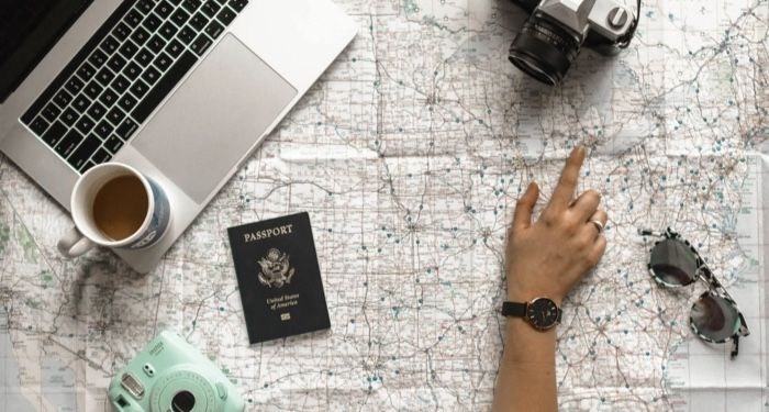 a hand posting to a location on a map. Scattered around the map are a passport, sunglasses, two cameras, and a laptop