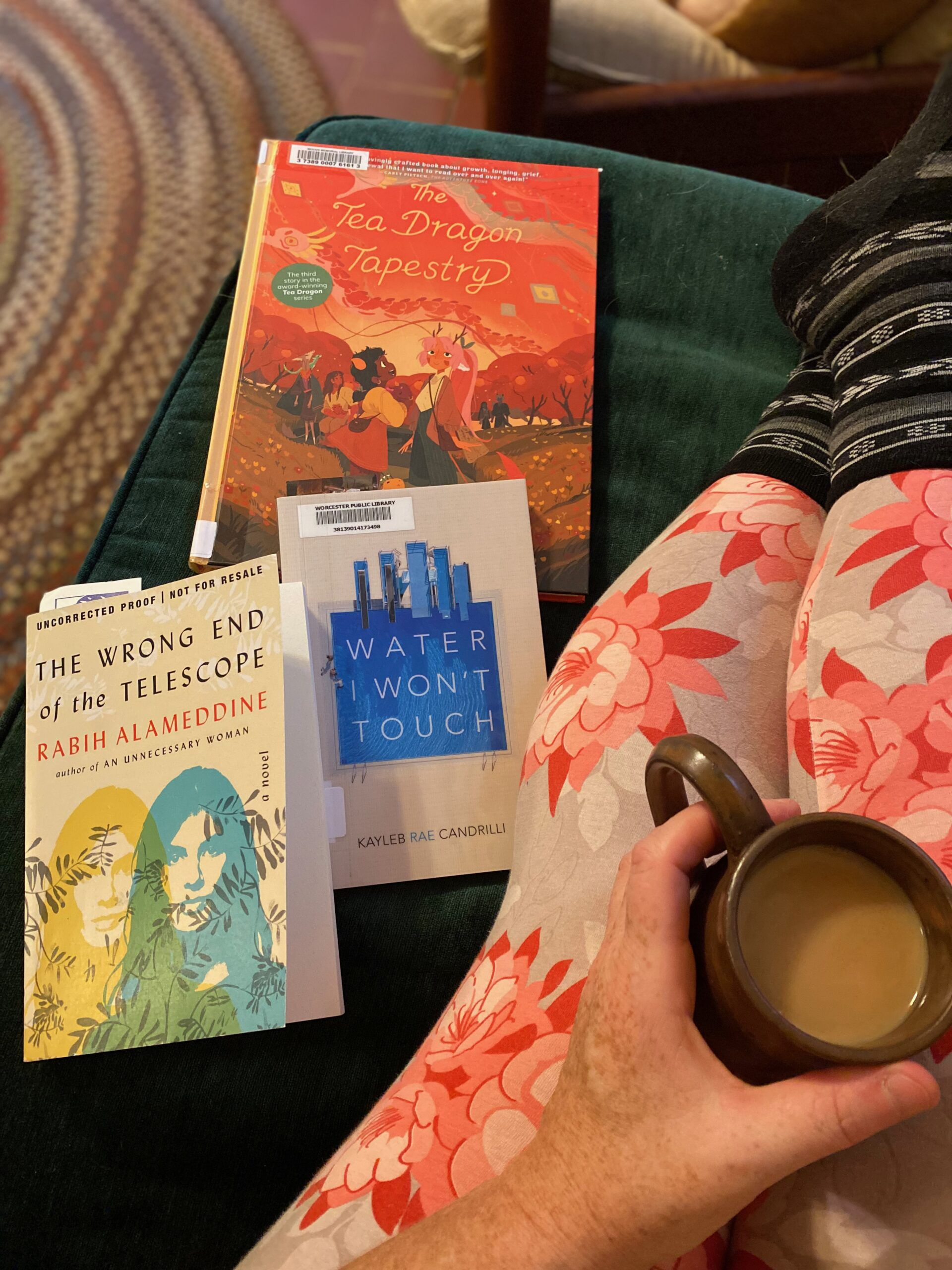 Image of my legs stretched out on a green couch. I am wearing leggings with large red flowers on them and holding a mug of tea. Three books ar on the couch next to me: The Tea Dragon Tapestry, Water I Won't Touch, and The Wrong End of the Telescope. Photo by me.