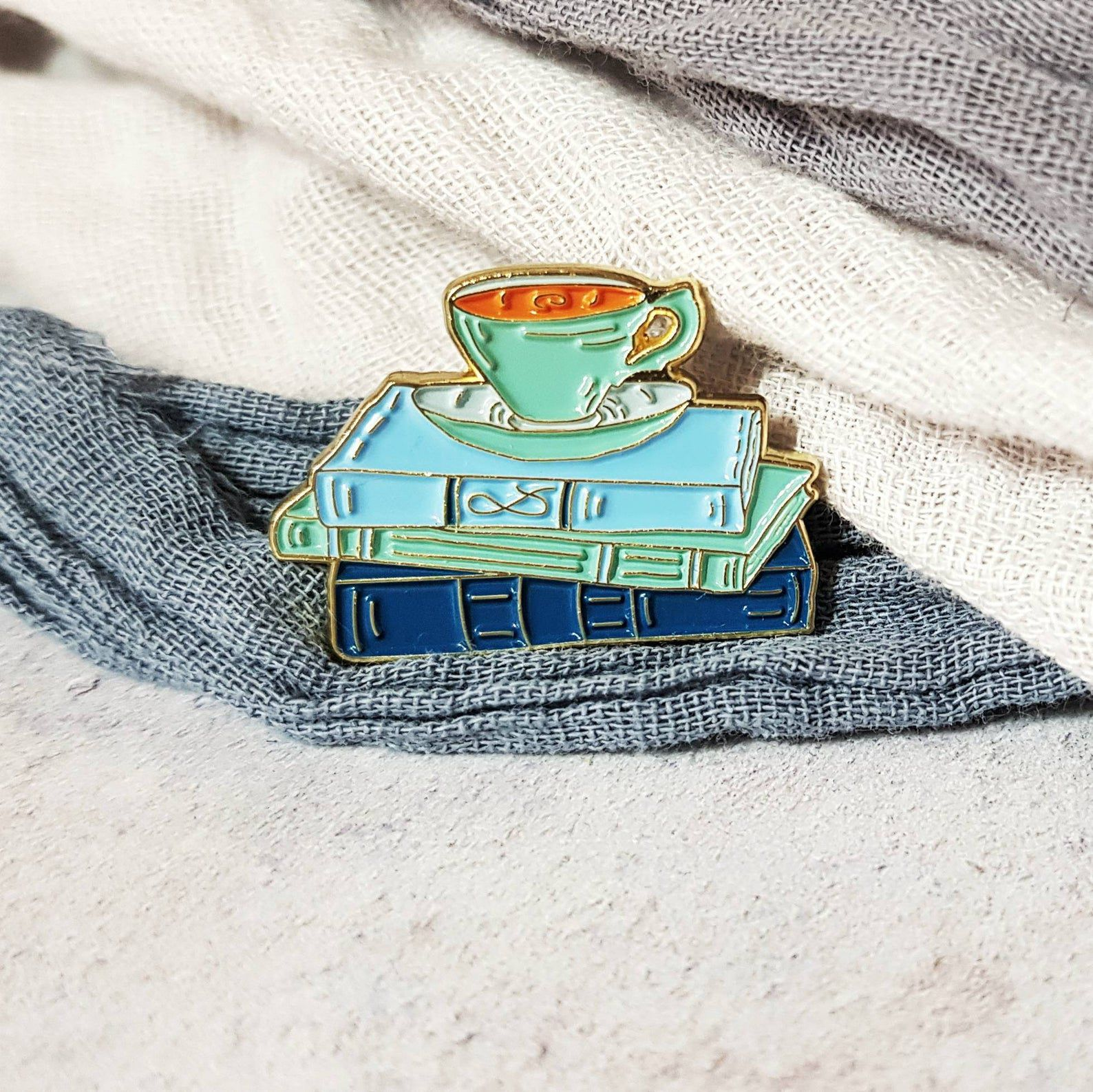 a blue and green enamel pin depicting a stack of books and a tea cup and saucer.