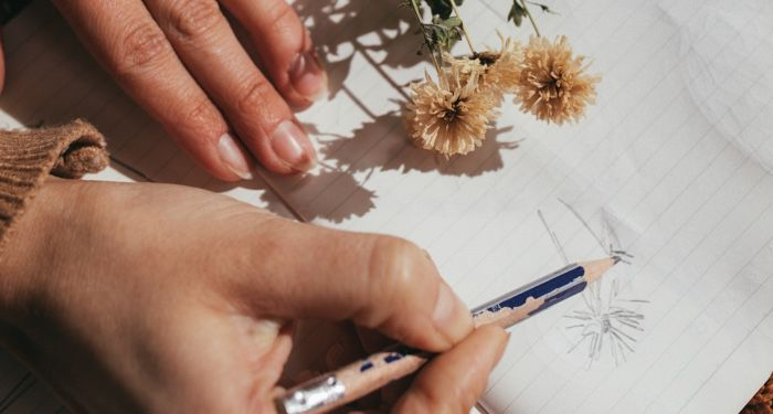 person drawing a flower on lined paper