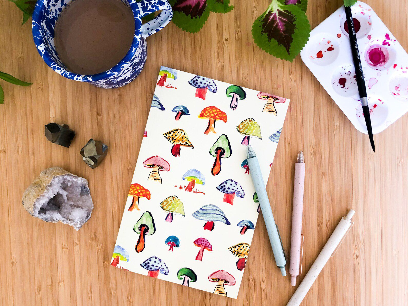 A white notebook, with a cover full of watercolor mushrooms.
