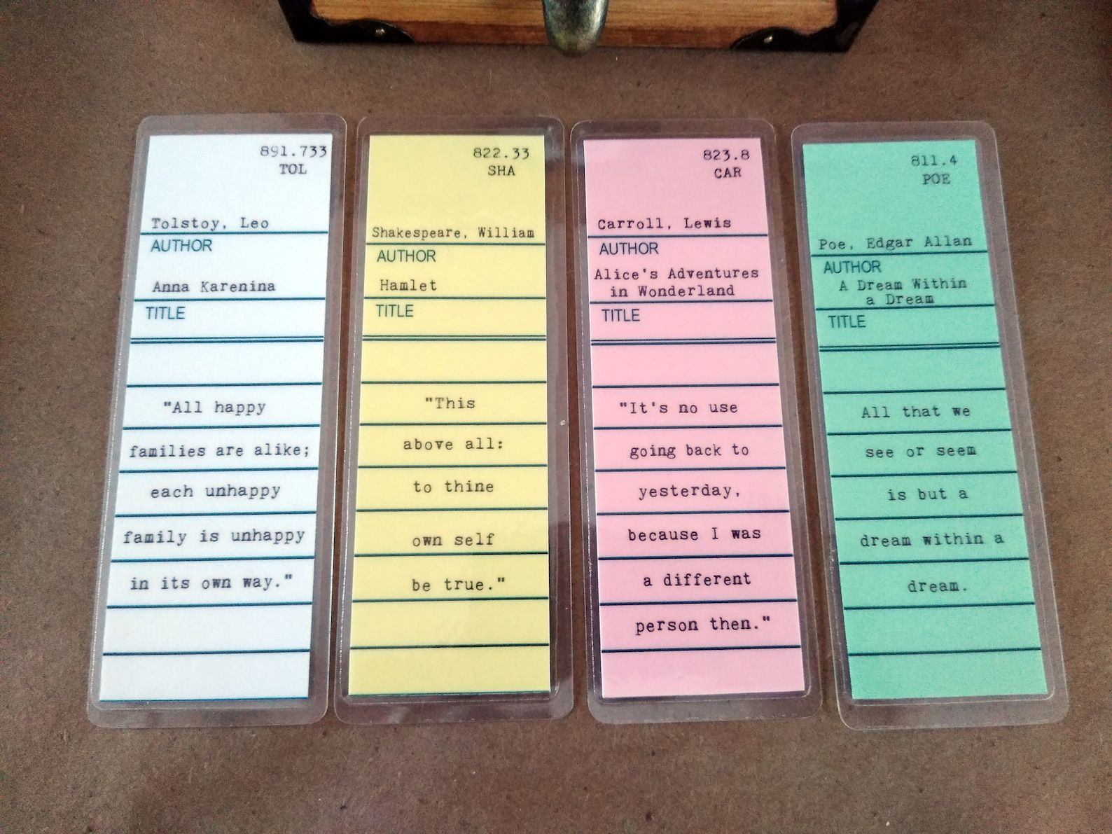Four bookmarks in the style of library cards featuring titles of various classic novels and a call number and famous quote from the book.