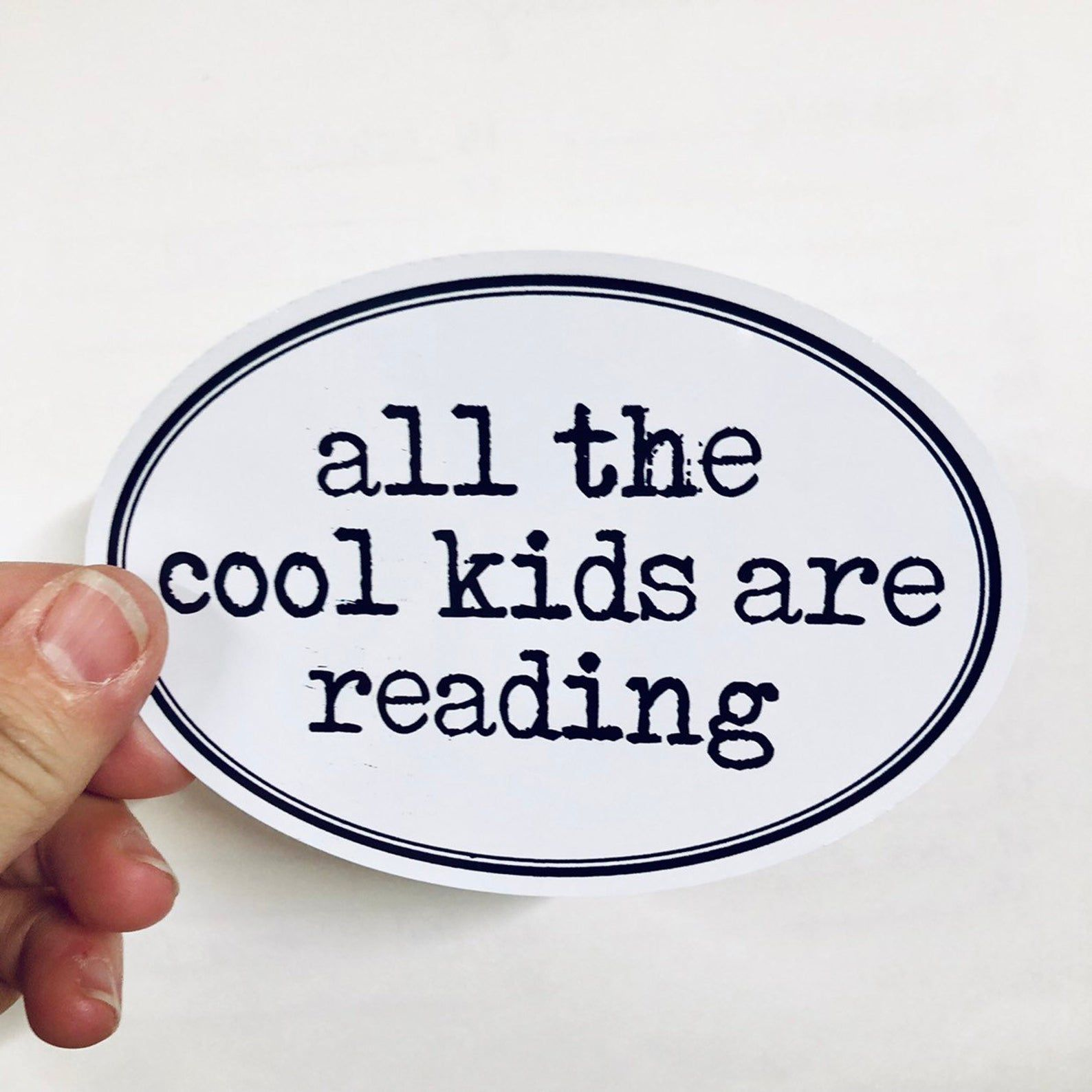 """Black and white oval sticker that reads """"all the cool kids are reading"""""""