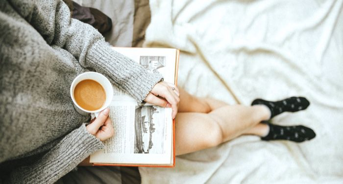 person holding a coffee cup and n open book on their lap
