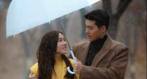 still shot from crash landing on you: man and women look into each other's eyes under an umbrella