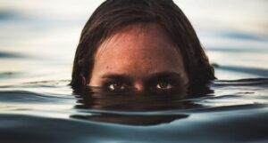 a person looks creepily with half of their face under water