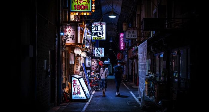creepy image of two people walking down a dark Japanese alleyway lit with neon signs