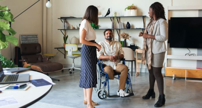 a team having a discussion in an office. Two women are standing, a man in a wheelchair is positioned between them