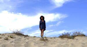 a woman in a dark blue dress short standing in the desert
